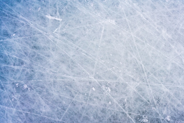 Fond de glace avec des marques de patinage et de hockey, texture bleue de la surface de la patinoire avec des rayures
