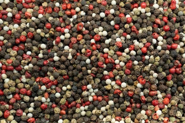 Fond de grains de poivre mélangés. grains de poivre de différentes couleurs, gros plan. vue de dessus.