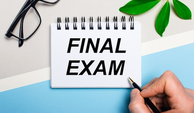 Sur un fond gris-bleu, près de lunettes et d'une feuille verte d'une plante, un homme écrit sur une feuille de papier le texte examen final. mise à plat. vue d'en-haut.