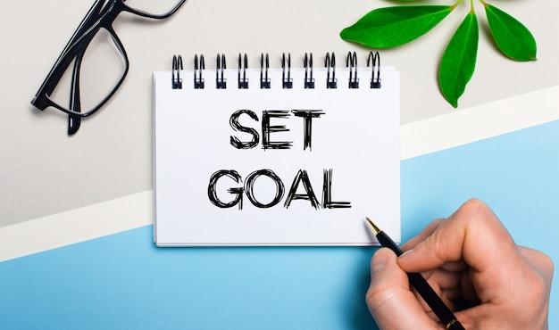 Sur un fond gris-bleu, près de lunettes et d'une feuille verte d'une plante, un homme écrit sur un morceau de papier le texte fixer un objectif. mise à plat. vue d'en-haut.