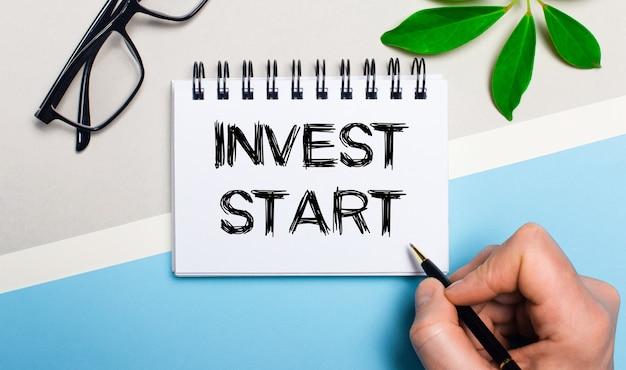 Sur un fond gris-bleu, près de lunettes et d'une feuille verte d'une plante, un homme écrit sur un morceau de papier le texte invest start. mise à plat. vue d'en-haut.