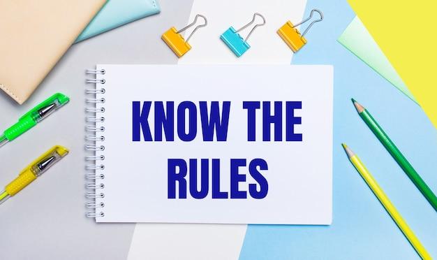 Sur un fond gris et bleu se trouvent des articles de papeterie de couleur jaune-vert, un cahier avec le texte connaissez les règles. mise à plat.