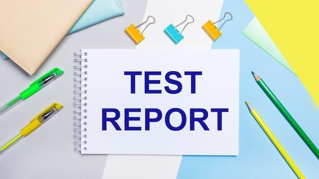 Sur un fond gris et bleu se trouvent du papier à lettres de couleur jaune-vert, un cahier avec le texte rapport d'essai. mise à plat.