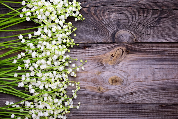 Fond gris en bois avec des fleurs fraîches lys de la vallée