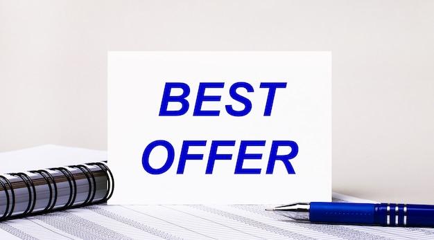 Sur un fond gris clair, un cahier, un stylo bleu et une feuille de papier avec le texte meilleure offre. concept d'entreprise