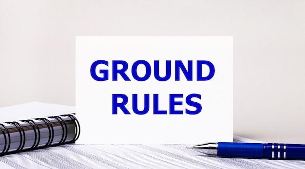 Sur un fond gris clair, un cahier, un stylo bleu et une feuille de papier avec le texte règles de base. concept d'entreprise