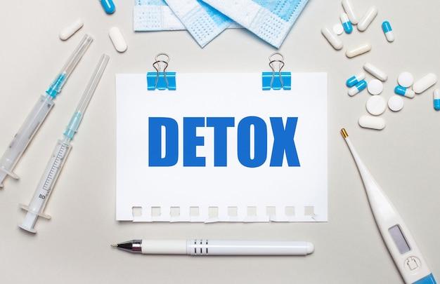 Sur fond gris clair, des masques médicaux bleus, des seringues, un thermomètre électronique, des pilules, un stylo et un cahier avec l'inscription detox. notion médicale
