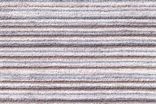Fond gris clair d'une matière textile tricotée. tissu avec un gros plan de texture rayée.