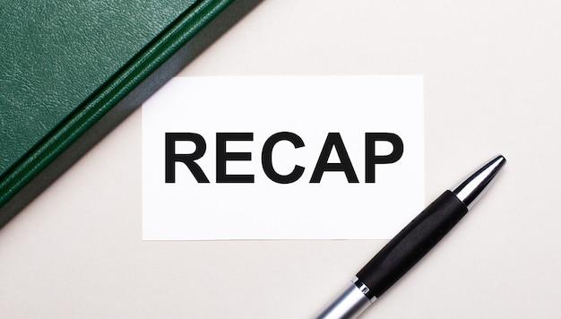 Sur un fond gris clair se trouvent un stylo, un cahier vert et une carte blanche avec le texte recap. concept d'entreprise.