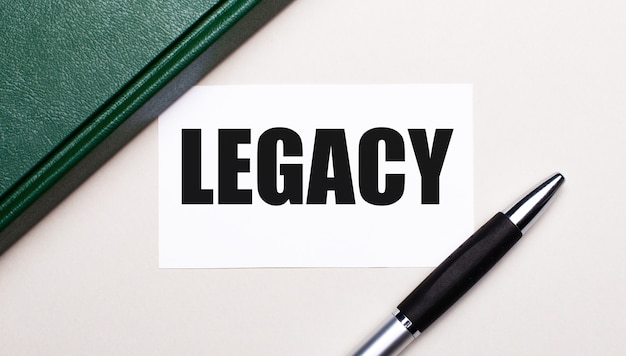 Sur un fond gris clair se trouvent un stylo, un carnet vert et une carte blanche avec le texte legacy. concept d'entreprise.