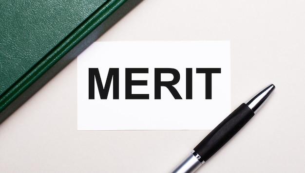 Sur un fond gris clair se trouvent un stylo, un carnet vert et une carte blanche avec le texte merit. concept d'entreprise.