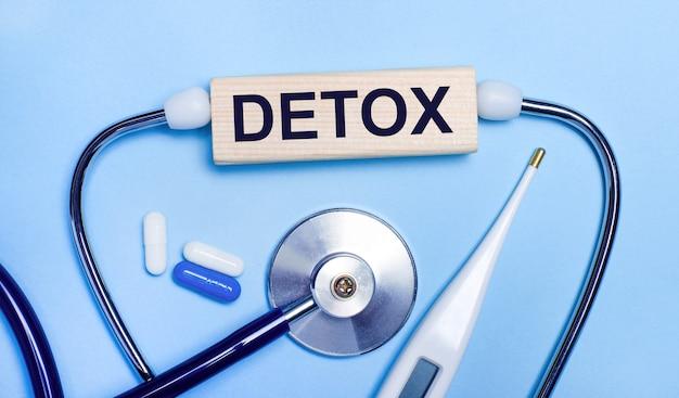 Sur un fond gris clair, un stéthoscope, un thermomètre électronique, des pilules, un bloc de bois avec le texte detox. notion médicale.