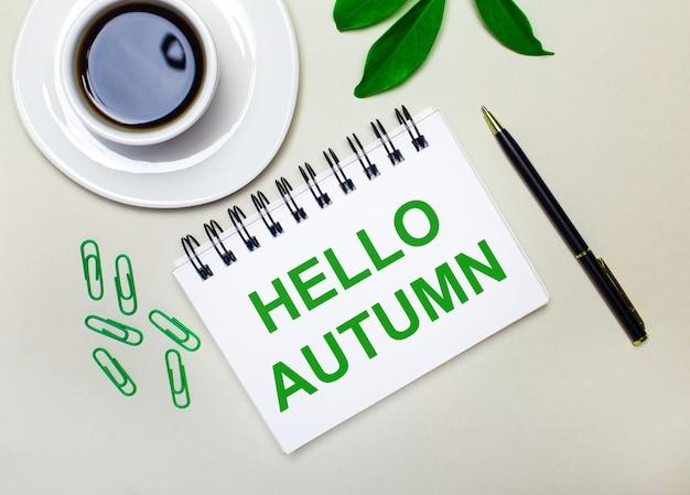 Sur un fond gris clair, une tasse de café blanche, des trombones verts et une feuille verte d'une plante, ainsi qu'un stylo et un cahier avec les mots bonjour automne.