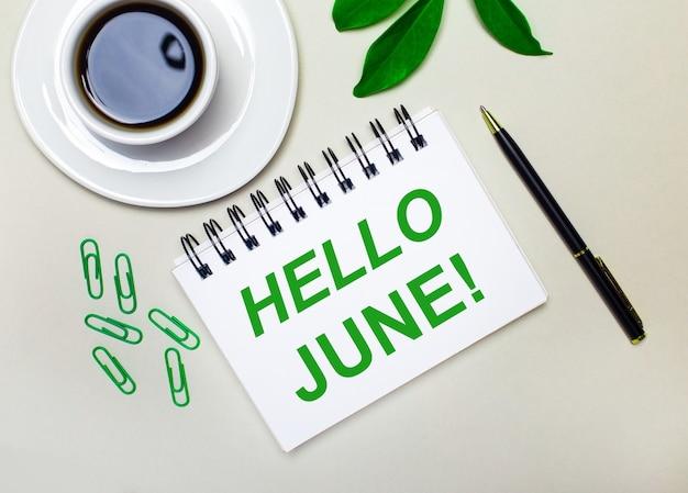 Sur un fond gris clair, une tasse de café blanche, des trombones verts et une feuille verte d'une plante, ainsi qu'un stylo et un cahier avec les mots bonjour juin.