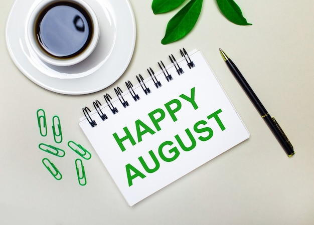 Sur un fond gris clair, une tasse de café blanche, des trombones verts et une feuille verte d'une plante, ainsi qu'un stylo et un cahier avec les mots happy august.