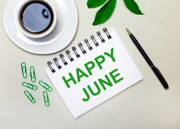 Sur un fond gris clair, une tasse de café blanche, des trombones verts et une feuille verte d'une plante, ainsi qu'un stylo et un cahier avec les mots happy june.