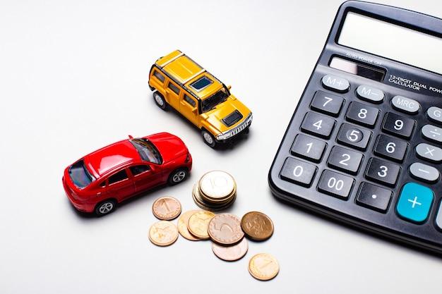 Sur un fond gris clair, des voitures rouges et jaunes, une calculatrice noire et des pièces de monnaie. concept d'entreprise
