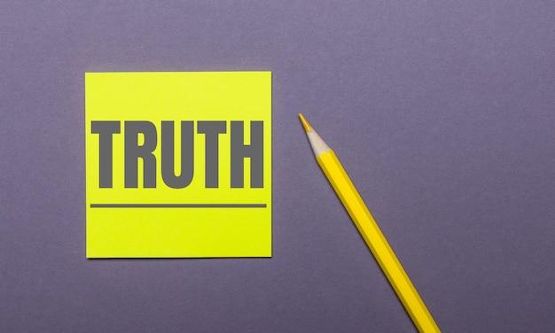 Sur fond gris, un crayon jaune vif et un autocollant jaune avec le mot vérité