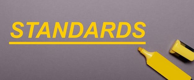 Sur fond gris, feutre jaune et inscription jaune normes