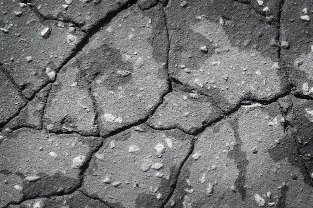 Fond gris fissuré en béton bitumineux