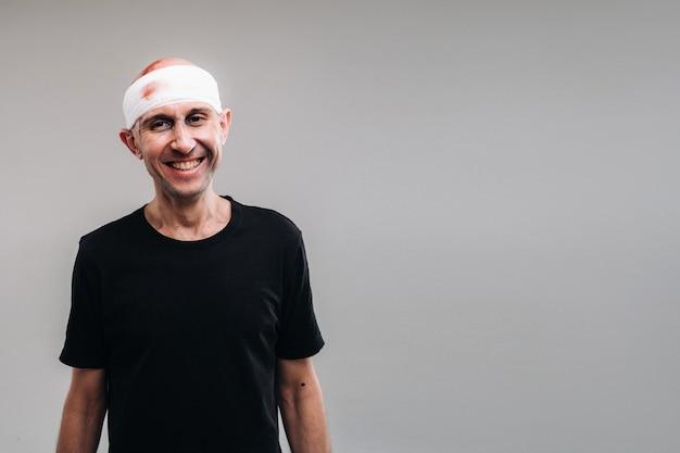 Sur un fond gris se dresse un homme battu et battu dans un t-shirt noir avec la tête enveloppée dans un bandage.