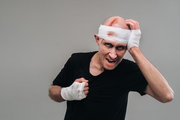 Sur un fond gris se tient un homme battu dans un t-shirt noir avec ses mains enveloppées