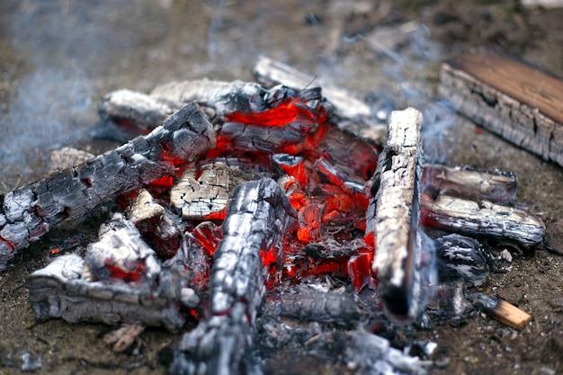 Fond de gros plan de charbons ardents rouges. briquettes de charbon de bois lumineuses.
