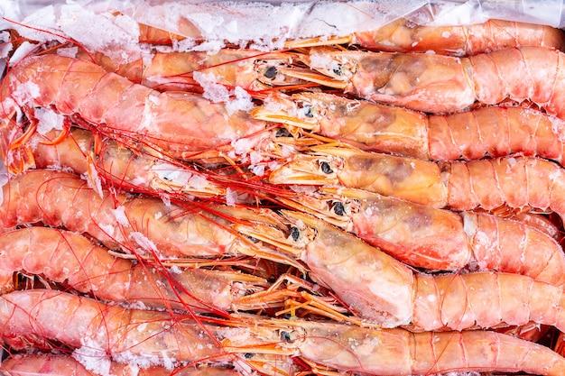 Fond de grosses crevettes rouges crues congelées.