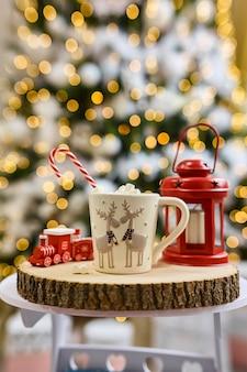 Fond de guirlandes lumineuses, chocolat chaud aux guimauves, tasse blanche avec cerf sur une coupe en bois et lanterne rouge et train pour enfants à la maison pendant les vacances de noël et du nouvel an. bokeh flou.
