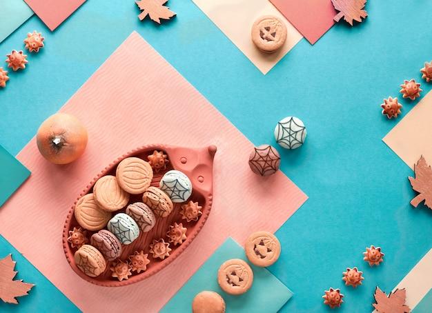 Fond d'halloween avec des biscuits à la citrouille et des bonbons sur du papier dans des couleurs pastel