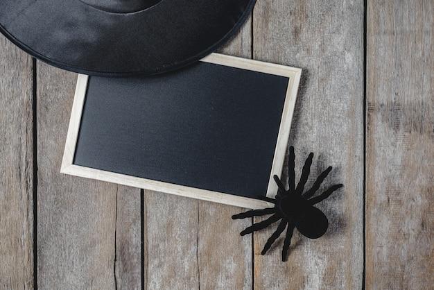 Fond d'halloween avec chapeau de sorcière, araignée noire et tableau noir sur plancher en bois