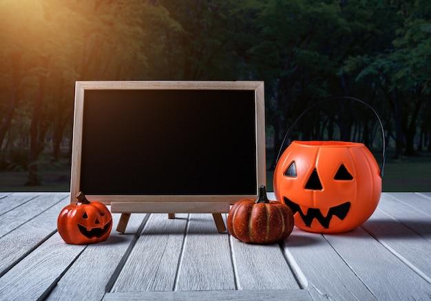Fond d'halloween citrouille effrayante, tableau noir sur plancher de bois et forêt sombre.