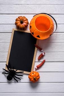 Fond d'halloween avec des citrouilles, araignée noire et tableau noir en bois