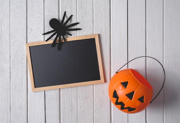 Fond d'halloween avec des citrouilles, araignée noire et tableau noir sur fond de plancher en bois