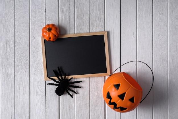 Fond d'halloween avec des citrouilles, araignée noire et tableau noir sur plancher en bois