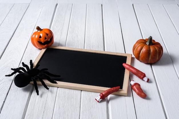 Fond d'halloween avec des citrouilles, une araignée noire et un tableau noir