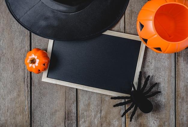 Fond d'halloween avec des citrouilles, chapeau de sorcière, araignée, doigts et tableau noir