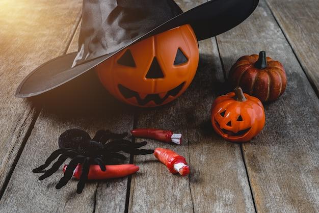 Fond d'halloween avec des citrouilles, chapeau de sorcière, araignée noire, doigts sur plancher en bois