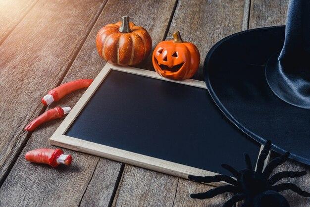 Fond d'halloween avec des citrouilles, chapeau de sorcière, araignée noire, doigts et tableau noir