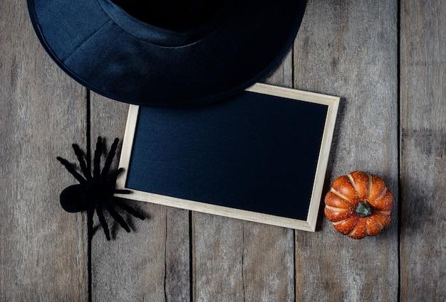 Fond d'halloween avec des citrouilles, chapeau de sorcière, araignée noire, tableau noir sur le plancher en bois ba