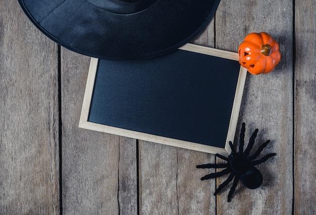Fond d'halloween avec des citrouilles, chapeau de sorcière, araignée et tableau noir sur plancher en bois