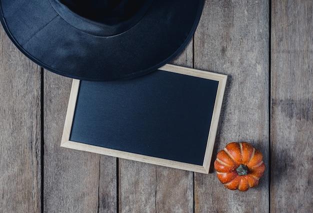 Fond d'halloween avec des citrouilles, chapeau de sorcière, tableau noir sur fond de plancher en bois