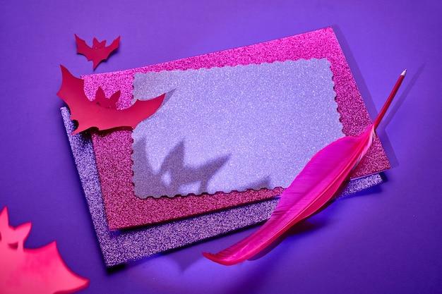 Fond d'halloween créatif en néon rose et violet brillant avec une pile de papier scintillant, plume et chauves-souris en papier. copiez-espace sur la carte supérieure.