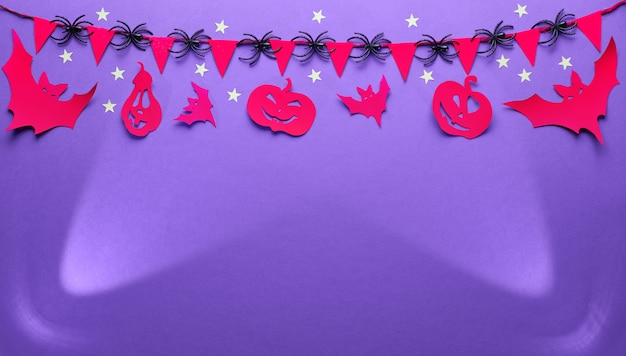 Fond d'halloween créatif en violet, rouge et noir, image plate, panoramique avec copie-espace. projecteurs, figurines en papier de chauves-souris et citrouilles jack lanterne, guirlande avec drapeaux et araignées.