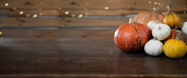 Fond d'halloween festif. de nombreuses citrouilles différentes se trouvent sur une table en bois. récolte d'automne de graines de citrouille. baner.