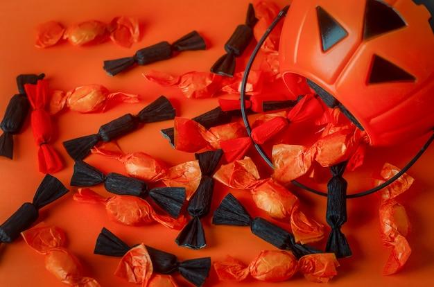 Fond d'halloween - gros plan de bonbons noirs et orange avec un sac de citrouille