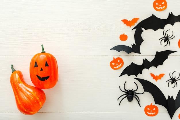 Fond d'halloween avec jack-o'-lanter, citrouilles, chauves-souris en papier, araignées, confettis sur fond de bois blanc. décorations de vacances d'halloween. mise à plat, vue de dessus. maquette d'invitation à la fête, célébration.
