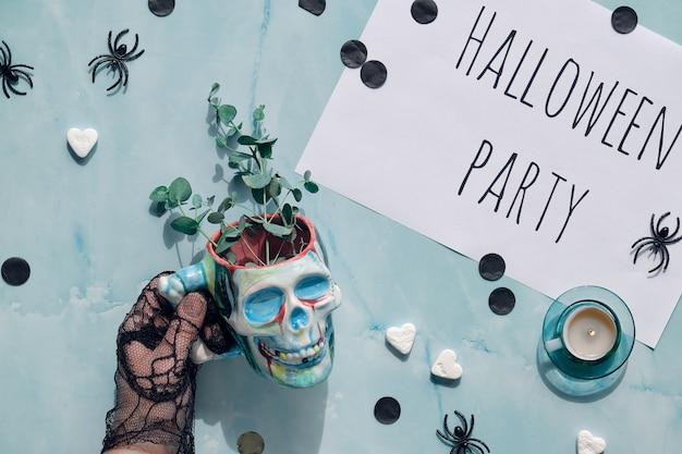 Fond d'halloween. la main dans un gant en filet noir tient la coupe du crâne avec des brindilles d'eucalyptus.