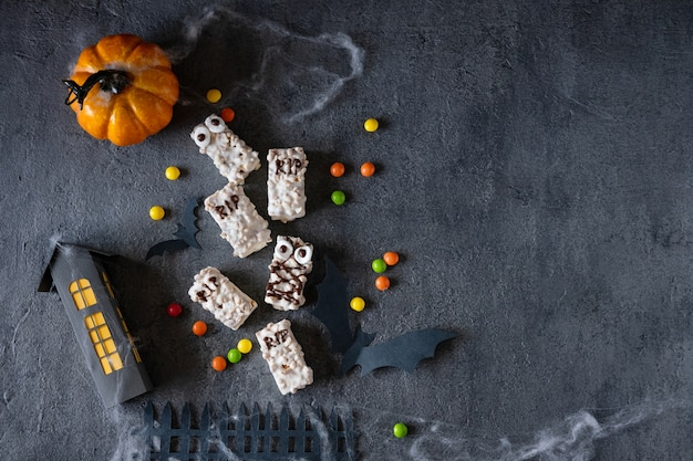 Fond d'halloween moderne. biscuits d'halloween. monstres drôles faits de biscuits au chocolat sur la table. décoration de fête d'halloween. tromper ou traiter le concept.