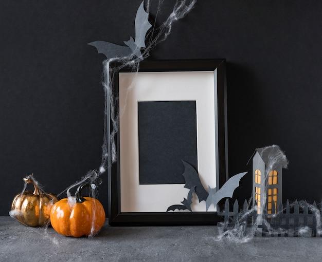 Fond d'halloween moderne avec des citrouilles, des chauves-souris et un cadre noir sur fond sombre